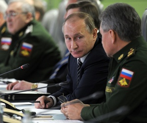 Russian President Vladimir Putin, second right, speak with Russian Defense Minister Sergei Shoigu, right, as he attends a meeting with top military and leaders of military industry in the Defense Ministry in in Moscow, Russia, Friday, March 11, 2016.