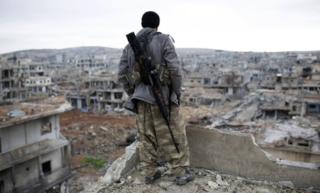 In this Jan. 30, 2015 file photo, a Syrian Kurdish sniper looks at the rubble in the Syrian city of Ain al-Arab, also known as Kobani.
