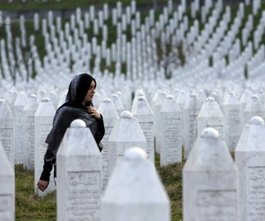 A Bosnian woman walks among gravestones at Memorial Centre Potocari near Srebrenica, Bosnia and Herzegovina.