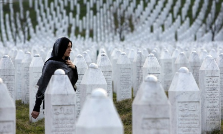A Bosnian woman walks among gravestones at Memorial Centre Potocari near Srebrenica, Bosnia and Herzegovina.
