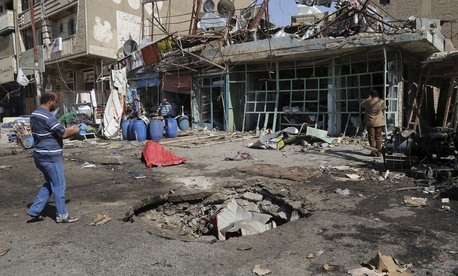 A civilian inspects a crater caused by a car bomb explosion in Baghdad, Iraq, Friday, Sept. 12, 2014.