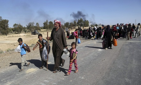 People flee their homes during clashes between Iraqi security forces and Islamic State group in Hit, 85 miles (140 kilometers) west of Baghdad, Iraq, Monday, April 4, 2016.