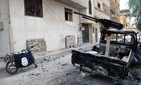In this photo released on Sunday March 27, 2016, by the Syrian official news agency SANA, a burned vehicle with machine gun is seen next to a motorcycle draped with the Islamic State group flag, in the ancient city of Palmyra, central Syria.