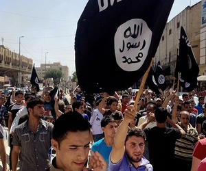 Demonstrators chant pro-Islamic State group slogans as they carry the group's flags in front of the provincial government headquarters in Mosul, Iraq.