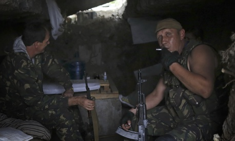 Pro-Russian rebels rest inside a shelter at their position outside Donetsk, eastern Ukraine, Friday, Aug. 22, 2014. Tensions between Russia and Ukraine escalated sharply on Friday as Moscow sent more than 130 trucks rolling across the border.