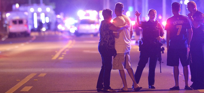 Orlando Police officers direct family members away from a fatal shooting at Pulse Orlando nightclub in Orlando, Fla., Sunday, June 12, 2016. (AP Photo