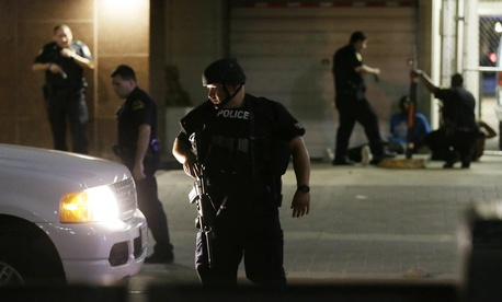 Dallas police detain a driver after several police officers were shot in downtown Dallas on July 7, 2016.