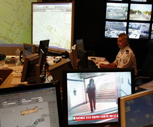 French Police officer checks on video monitors and computer screens in the underground security central command center of the Paris prefecture