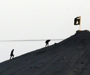 Militants with the Islamic State group are seen after placing their group's flag on a hilltop at the eastern side of the town of Kobani, Syria, Oct. 6, 2014.
