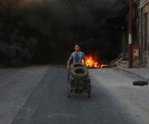 This July. 31, 2016 photo, provided by the Syrian anti-government activist group Aleppo Media Center (AMC), shows a Syrian young man burns tyres in an attempt to prevent airstrikes above Aleppo, Syria.