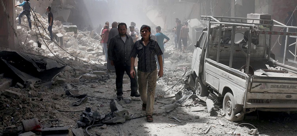 This July. 26, 2016 file photo, provided by the Syrian anti-government activist group Aleppo Media Center (AMC), shows Syrian citizens inspect damaged buildings after airstrikes hit Aleppo, Syria.
