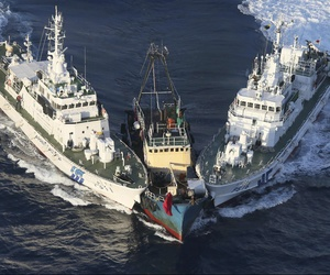 A boat, center, is surrounded by Japan Cost Guard's patrol boats after some activists descended from the boat on Uotsuri Island, one of the islands of Senkaku in Japanese and Diaoyu in Chinese, in East China Sea, Aug. 15, 2012.