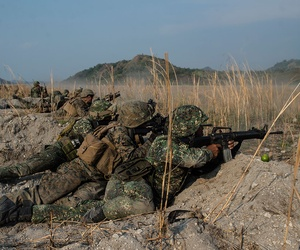 "U.S. and Philippine Marines fire their rifles ""shoulder-to-shoulder"" during Balikatan 16, at Crow Valley, Philippines in April."
