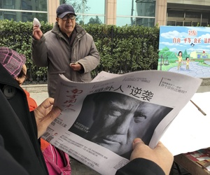 """In this Nov. 10, 2016 file photo, a Chinese man holds up a Chinese newspaper with the front page photo of U.S. President-elect Donald Trump and the headline """"Outsider counter attack"""" at a newsstand in Beijing, China."""