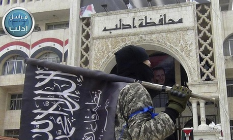 A fighter from Syria's al-Qaida-linked Nusra Front holds his group flag as he stands in front of the governor building in Idlib province, north Syria, March 28, 2015.