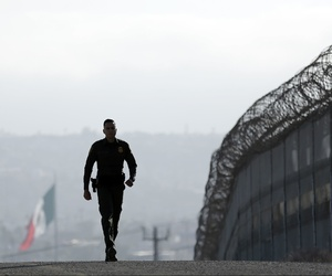 Border Patrol agent Eduardo Olmos walks near the secondary fence separating Tijuana, Mexico, background, and San Diego in San Diego, June 22, 2016.