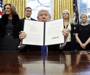 "President Donald Trump holds up another of his executive actions signed in his first two weeks, this one directing his administration to ""develop a comprehensive plan to defeat ISIS."""