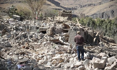 A man walks amid the rubble of a house destroyed by a Saudi-led airstrike on the outskirts of Sanaa, Yemen, Thursday, Feb. 2, 2017.