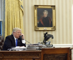 President Donald Trump speaks on the phone with Prime Minister of Australia Malcolm Turnbull, with National Security Adviser Michael Flynn, center, and chief strategist Steve Bannon, right, in the Oval Office of the White House, Jan. 28, 2017.