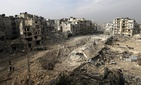 People walk through mounds of rubble which used to be high rise apartment buildings in the once rebel-held Ansari neighborhood in the eastern Aleppo, Syria on Jan. 20, 2017.