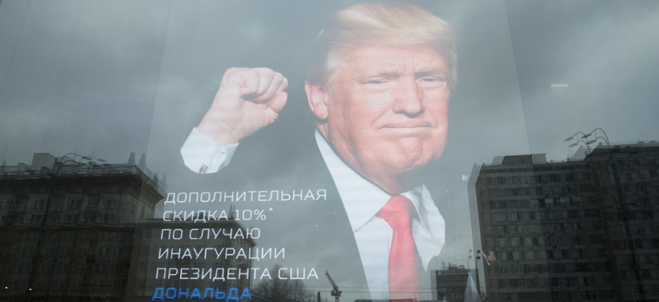 """The U.S. Embassy building is reflected in a window of a Russian military outerwear shop """"Armia Rossii"""" (Russian Army) displaying a poster of Donald Trump, in downtown Moscow, Russia, Friday, Jan. 20, 2017."""