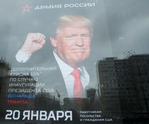 "The U.S. Embassy building is reflected in a window of a Russian military outerwear shop ""Armia Rossii"" (Russian Army) displaying a poster of Donald Trump, in downtown Moscow, Russia, Friday, Jan. 20, 2017."