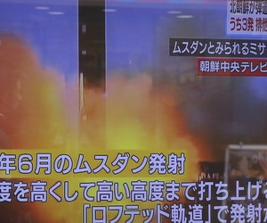 A man walks past a screen showing a TV news on North Korea's missile firing, in Tokyo, Monday, March 6, 2017.