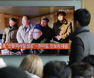 People in Seoul, South Korea watch a TV news program showing North Korean leader Kim Jong Un.