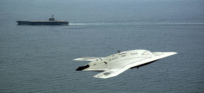 n X-47B Unmanned Combat Air System (UCAS) demonstrator flies near the aircraft carrier USS George H.W. Bush.