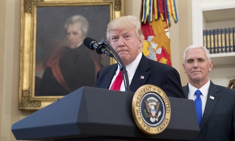 President Donald Trump, accompanied by Vice President Mike Pence,takes the podium in the Oval Office at the White House, March 31, 2017, in Washington.