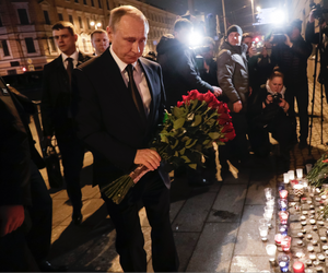 Russian President Vladimir Putin, second left, lays flowers at a place near the Tekhnologichesky Institut subway station in St.Petersburg, Russia, Monday, April 3, 2017.