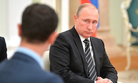 In this photo taken on Tuesday, Oct. 20, 2015, Russian President Vladimir Putin attends his meeting with Syrian President Bashar Assad, back to the camera, in the Kremlin in Moscow, Russia.