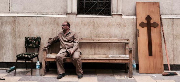 A man sits on a bench outside a church after a bomb attack in the Nile Delta town of Tanta, Egypt, Sunday, April 9, 2017.