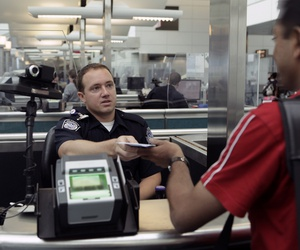 A CBP Officer processes an incoming passenger at the Newark International Airport in 2010.