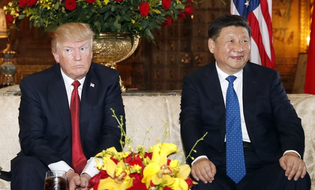 President Donald Trump and Chinese President Xi Jinping, sit as they pose for photographers before a meeting at Mar-a-Lago on April 6, 2017, in Palm Beach, Fla.