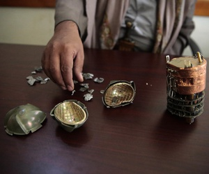 A Yemeni official displays cluster bomblet fragments from an unidentified source at a police compound in Sanaa, Yemen, Oct. 5, 2016.