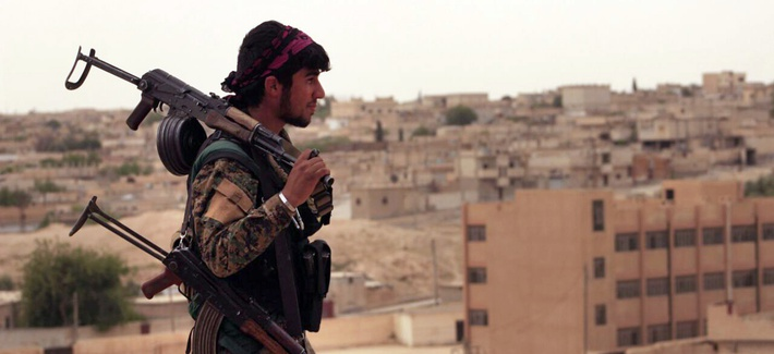A Syrian Democratic Forces fighter carrying weapons as he looks toward the northern town of Tabqa, Syria, Apr 30, 2017.