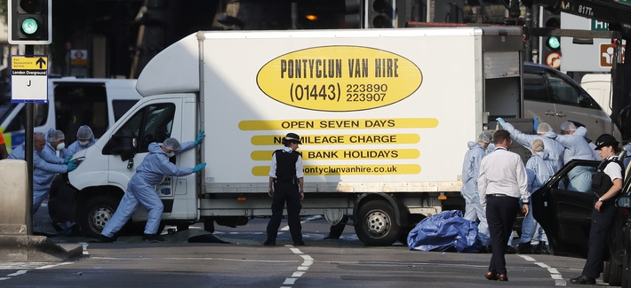 Forensic officers move the van that struck pedestrians near a mosque in north London early Monday morning.