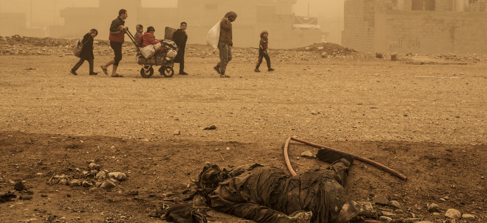 A group of civilians pass close to the body of an Islamic State militant, while fleeing from Mosul due to ISIS heavy shelling in several areas under control of the Iraqi Army, Mosul, Iraq, Friday, Dec. 2, 2016.