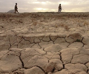 Two men walk along a ridge behind the cracked earth that should be a wheat field in Salawath, Afghanistan, March 10, 2002.