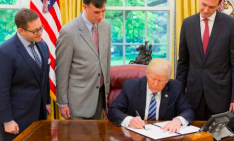 President Donald Trump signs a May 11, 2017, order on cybersecurity.