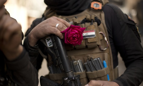 An Iraqi special forces soldier wears a rose in his body armor as troops move from the Yarmouk neighborhood to take another district from Islamic State militant control in Mosul, Iraq, Wednesday, April 12, 2017.