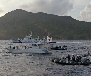 Japanese Coast Guard vessel and boats, rear and right, sail alongside Japanese activists' fishing boat, center with a flag, warning the activists away from a group of disputed islands called Diaoyu by China and Senkaku by Japan, early Sunday Aug 18, 2013.