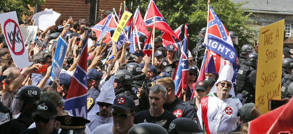 Members of the KKK are escorted by police past a large group of protesters during a KKK rally Saturday, July 8, 2017, in Charlottesville, Va.