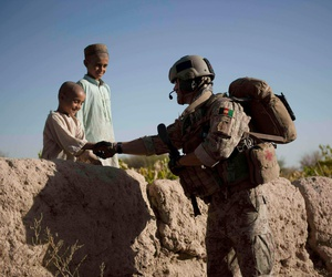 A U.S. Army Green Beret greets Afghan children during a foot patrol in Kandahar province, September 2010.