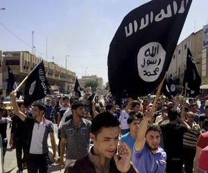 Demonstrators chant pro-ISIS slogans as they carry the group's flags in front of the provincial government headquarters in Mosul in 2014.