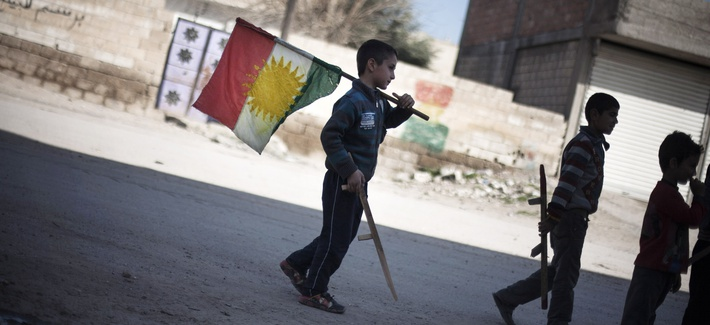 In this Monday, Feb. 26, 2013 file photo, a boy carries a Kurdish flag as he and others hold toy guns.