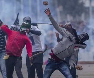 Masked Kashmiri protesters throw rocks at government forces during a protest outside Eidgha, a prayer ground, in Srinagar, Indian controlled Kashmir, Saturday, Sept. 2, 2017.