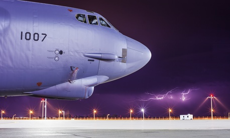 Lightning strikes behind a B-52H Stratofortress at Minot Air Force Base, N.D.