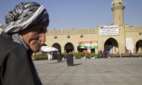 Saber Salim sits outside Irbil's Citadel near a campaign poster urging people to vote 'yes' in September's schedule referendum on independence from Iraq, Aug. 24, 2017.